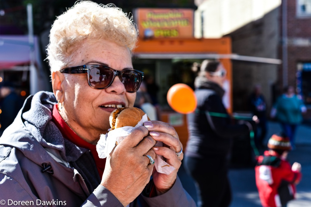 Marilyn Dawkins tasting the pumpkin burger Circleville Pumpkin Show 2018